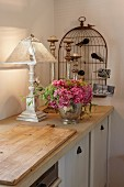 Shabby chic decor with bouquet of hydrangeas and stylised birdcage on rustic kitchen counter