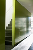 Staircase hidden behind yellow wall with integrated cupboards