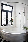 Traditional corner bathtub against tiled wall below window with dark frame