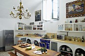Converted former monastery with barrel vaulted ceiling and masonry kitchen counter; large still-life oil paintings above kitchen shelves