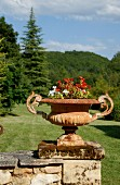 Planted metal urn on stone wall in front of wooded landscape