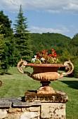 Bepflanzte Metall-Amphore auf Natursteinmauer vor bewaldeter Landschaft