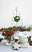 Posy of holly berries, wire Christmas tree and place setting with biscuit on table