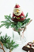 Chocolate Father Christmas lolly and conifer twig in jar