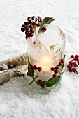 Ice lantern with holly berries in snow
