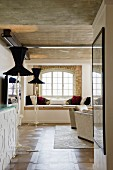 View into loft-style interior with window seat in niche and designer standard lamps with black lampshades below exposed concrete ceiling