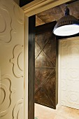 Open interior door with raised, carved designs and view into hallway with industrial ceiling lamp