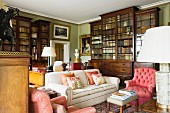 Upholstered chairs and sofa in front of traditional bookcases in library of English country house