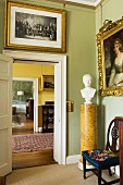 Gilt-framed paintings and bust of a man on marble pedestal; view through suite of rooms in English manor house