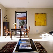 Sunny dining area with designer chairs and view of terrace through open door; ottoman on kilim rug