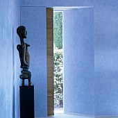 African sculpture on pedestal in blue foyer with view into garden through sliding wooden door