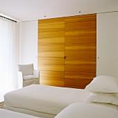 Eingebauter Schlafzimmerschrank mit interessantem Kontrast durch seitlich unauffällig weisse Türen und massgefertigte Holzelemente