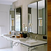 Large double washstand with Corian countertop and asymmetrical tilting mirrors on concrete partition
