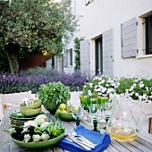 Aubergines, herbs and cutlery on wooden table outside modern Mediterranean holiday home; flowering lavender in background