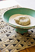Ammonit mit Sand in Keramikschüssel auf gemusterter Webdecke