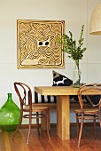 Square, expressionist artwork on wall; solid wooden table, bench, vintage bistro chairs and old oil bottle used as floor vase in foreground