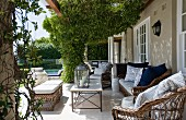 Large terrace with climber-covered pergola above rattan furniture outside traditional country house