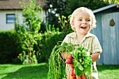 Germany, Bavaria, Boy holding radish and carrots, smiling