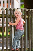 Germany, Girl standing on fence in playground