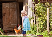 Germany, Bavaria, Girl with chicken on farm