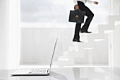 Spain, Businessman cimbing up stairs, laptop in foreground