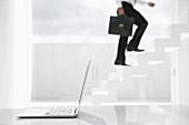 Geschäftsmann geht eine Treppe hinauf, Laptop im Vordergrund