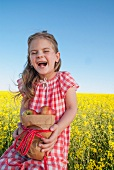 Girl holding sack of apples in field of oil-seed rape