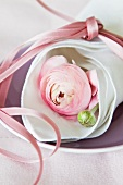Pink ranunculus wrapped in linen napkin tied with pink ribbon