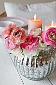 Ranunkelstrauss in silber glänzender Vase vor brennenden Kerzen