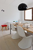 White plastic shell chairs at a modern dining table under a black, circular hanging light in a minimalist room