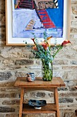Colourful modern painting on rustic stone wall; magnificent bouquet of calla lilies on small console table