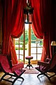 Antike Stühle mit pinkfarbenem Samtbezug vor Terrassentür mit rotem Vorhang und Blick in Gartenanlage