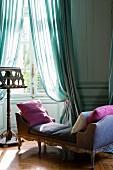 Rokoko Recamiere mit Samtbezug und Kissen vor Notenständer am Fenster mit drapierten, luftigen Vorhängen