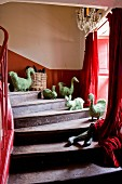 Straw animal figurines on treads of old wooden staircase and red curtains at window
