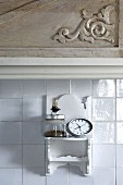 Weiss lackiertes Hängeregal im orientalischen Stil an weisser Fliesenwand unter Hängeschrank mit geschnitztem Holzdetail auf Tür