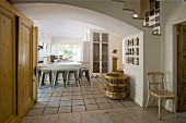 Wooden cupboard in wide, arched open doorway leading to kitchen