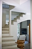 View through foyer past winding staircase in open-plan stairwell to white armchair in doorway