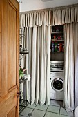 View through open door of washing machine and shelving behind floor-length curtains