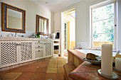 Spacious bathroom with washstand and base units on terracotta floor opposite bathtub below window