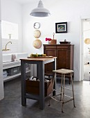 Original sink unit with two china basins and wall-mounted tap fitting in converted kitchen with vintage cupboard and simple work bench below pendant lamp