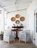Colonial-style veranda with white rattan chairs and antique wooden table