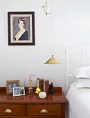 Antique chest of drawers in bedroom with white metal bed; portrait of woman on wall next to gold pendant lamp