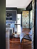 Offener Wohnraum in dezenten Grautönen und Natursteinquader im Kontrast zu anthrazitfarbenen Wänden