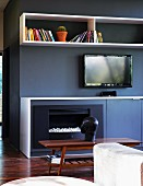 Fitted units in anthracite and white with integrated fireplace, sideboard, shelves and TV opposite sofa