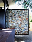 Stone partition element screening wooden terrace of residential house