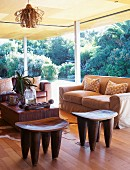 Seating area with sofa, African wooden stools & coffee table in interior with open sliding doors leading to garden