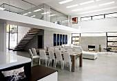 Offener, grosszügiger Designer Wohnraum mit Essplatz auf Estrichboden und Blick auf umlaufende Galerie mit Treppenaufgang in zeitgenössischer Architektur