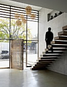 Minimalist staircase with floating wooden treads in foyer with glass facade and open front door