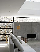 Pale grey sofa in front of wooden designer arc lamp in contemporary interior with open fireplace in exposed concrete wall