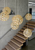 Pendant lamps with spherical, woven lampshades in foyer with floating staircase on exposed concrete wall
